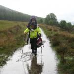 Ernie carries Jean through a puddle